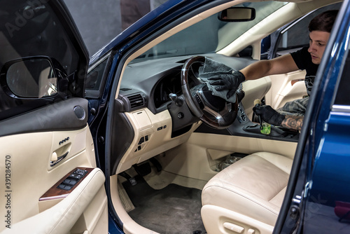 Vászonkép worker cleaning car steering wheel with microfiber cloth