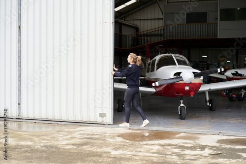 Vászonkép Woman opening the door of the hangar where there are several planes