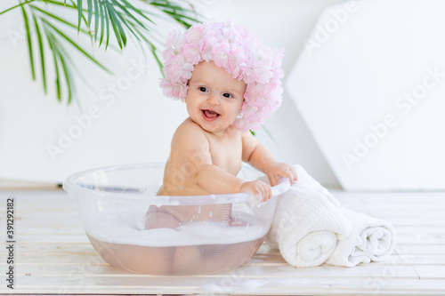 Canvas happy little baby girl washes in a basin with foam and water in a bright room at