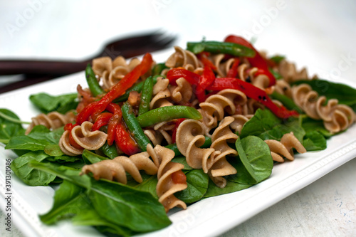 Close up of pasta primavera on bed of arugula