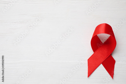 Fototapeta Top view of red ribbon on white wooden background, space for text. AIDS disease awareness obraz
