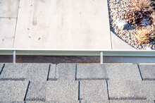 Top View Of A Gutter System On A Residential House.  Asphalt Shingles And Support Brackets Visible.