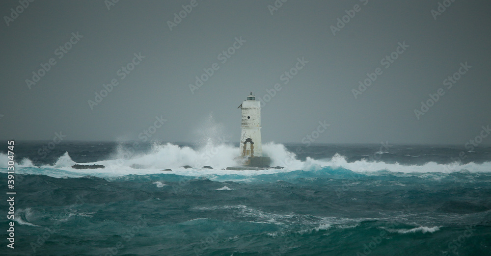 Fototapeta The lighthouse of the Mangiabarche shrouded by the waves of a mistral wind storm