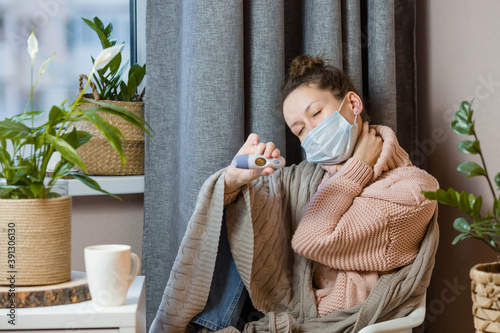 Fotografija Sick European attractive young woman caught a cold and looks at the thermometer Upset young blonde in a sweater and blanket feels bad, wears a medical mask