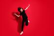 Leinwandbild Motiv Photo portrait full body view of crazy girl dancing standing on one leg isolated on vivid red colored background
