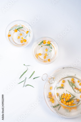 Fényképezés sea buckthorn berries are brewed in a transparent teapot on a white table and next to them are two transparent mugs with poured tea with sea buckthorn berries