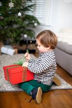 Young Boy Sitting On Living Room Floor, Unwrapping Christmas Present In Red Box.