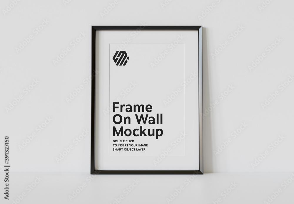 Fototapeta Vertical Black Frame Leaning on White Interior Mockup