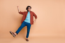 Full Length Photo Of Guy Dance Open Mouth Raise Fist Leg Wear Specs Brown T-shirt Trousers Footwear Isolated Beige Color Background