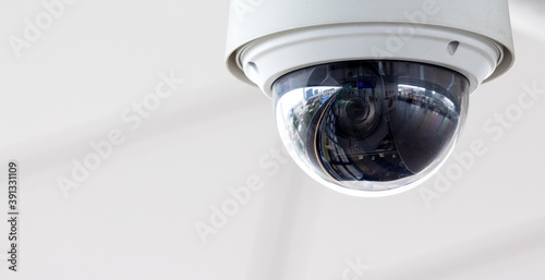 Fotografiet Closeup of white dome type cctv digital security camera installed on ceiling for observation