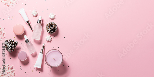 Long wide banner with skin care cosmetic products in unbranded containers and Christmas sparkling decorations on pink pastel background. Festive cosmetic sale.