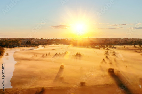Cuadros en Lienzo Autumn fog over the field and shadows from trees and bushes in the countryside next to the river, view of a drone flight from a height