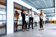 Group of attractive business people standing and communicating together, holding cups, in a modern office. Coffee break.