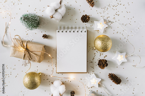 Obraz Christmas festive decorations and notebook. With wish list and 2021 goals concept. Notebook mock up, gift, and coton branch with shiny golden balls.New year flat lay, top view, copy space.. - fototapety do salonu