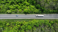 Aerial. Gasoline Fuel Truck Driving By The Highway Road Between Green Forest. Top View.