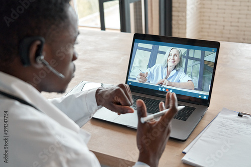 Black male doctor consulting senior old patient by telemedicine online video call Fototapeta
