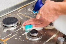 Man Hand Cleaning Gas Stove Using Sponge And Detergents. Cleaning A Gas Stove With Kitchen Utensils, Household Concepts, Or Hygiene And Cleaning