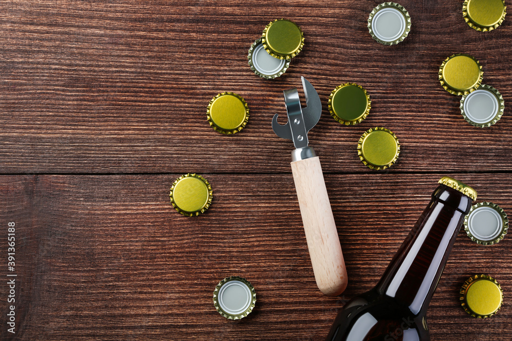 Fototapeta Bottle caps with bottle and opener on brown wooden table