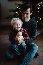Toddler (little Boy) Holding A Doll And Sitting On His Fathers Lap In Front Of The Christmas Tree With Christmas Lights