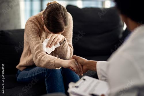 Fotografiet Depressed woman seeking solace from her psychotherapist.