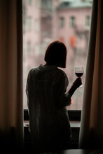 Silhouette Of A Young Girl In A White Shirt With Short Hair, Stands Near The Window With A Glass Of Wine