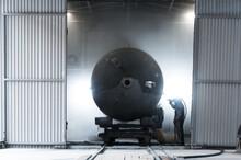 Factory Worker Sandblasting The Tank