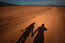 Shadow Of A Couple Holding Each Other's Hands As The Stand In The Middle Of A Desert Road