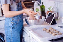 Woman Preparing Cookies With An Online Video Tutorial.