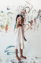 Little Girl In Dress Painting On Large White Paper In Garage