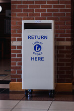 """White Library Book Return Bin With The Words """"Return Library Books Here"""" On The Front."""