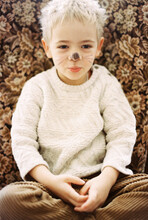 Toddler Boy With Face Paint In A Vintage Chair
