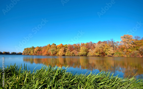 Reflection of a beautiful autumn forest in the river, against the background of Billede på lærred