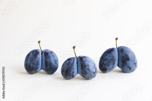 Obraz na plátně Ugly organic blue double plums heart-shaped on a white background