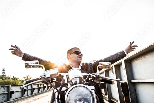 portrait of biker man in sunglasses sits on chopper motor bike on sunset sky Sta Canvas Print