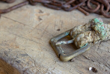A Very Old Buckle On A Dog Chain On Top Of A Wooden Table Next To A Rusted Chain