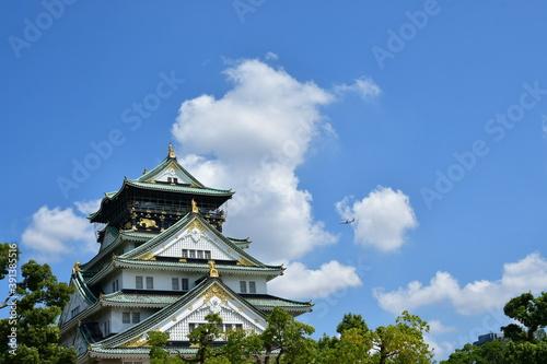 青空と大阪城上空を飛ぶ飛行機 Fotobehang