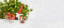 Shopping For Christmas Presents. Reindeer In Santa Hat And Shopping Cart With Many Gifts In Snow, Fir Tree And Bokeh Lights In Background. Winter Holiday Celebration. Banner With Copy Space