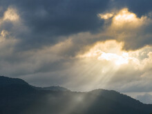 Mountain And Sunbeam Penetrating The Rain Clouds In A Dark Atmosphere.