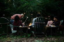 Black Friends Gathering Around Fire-pit Roasting Marshmallows And Eating Smores Having A Good Time