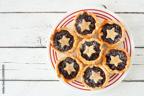 Plate of Christmas mincemeat tarts. Top view over a white wood background.