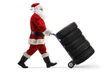 Full Length Profile Shot Of A Santa Claus Pushing Car Tires On A Hand Truck