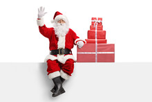 Full Length Portrait Of A Santa Claus With Presents Sitting On A White Banner And Waving