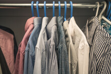 Clothing On Hangers In A Walk-in Closet With Mens Dress Shirts