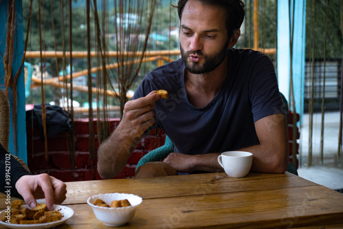 Closeup of a young Caucasian man tasting a snack in a restaurant Canvas