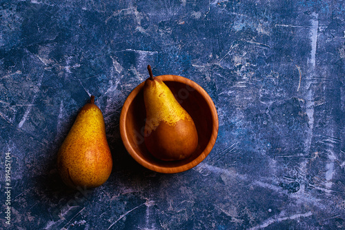 Top view of two pears, one in a wooden bowl, the other next to it on abstract bl Canvas Print