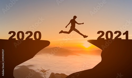 Silhouette of man jump to New year 2021 at sunrise with mist cover moutain, Happy New year 2021 concept