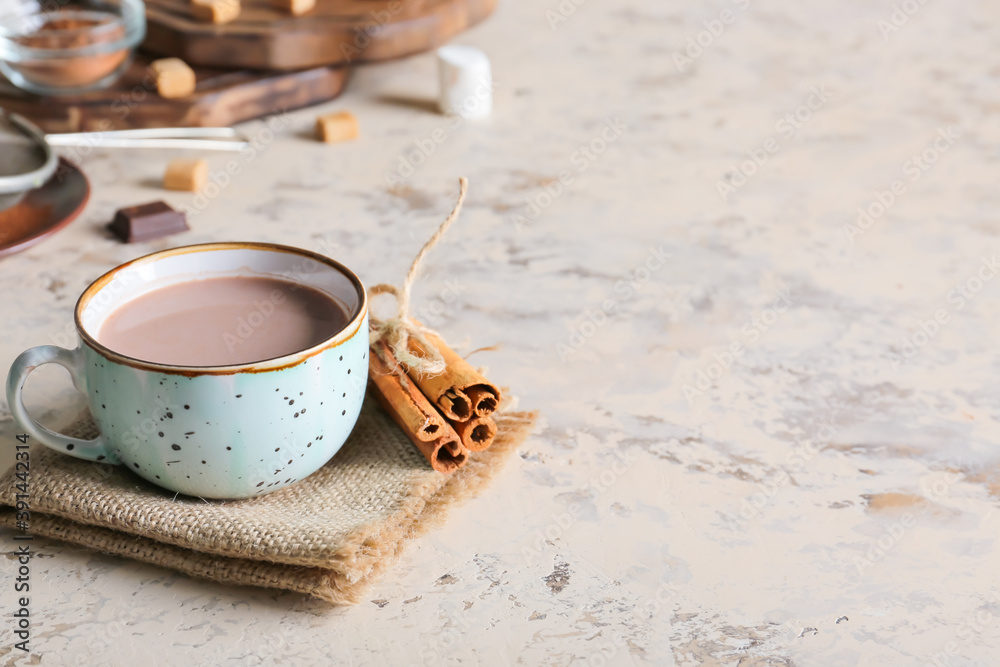 Fototapeta Cup of hot cacao drink with cinnamon on grey background