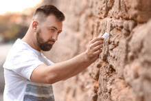 Man Placing Note In The Wailing Wall