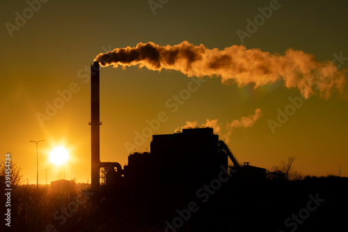 Fotografiet Air pollution site with a smoking factory or power plant chimney silhouette duri