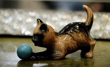 Closeup Of A Ceramic Cat Statue Playing With A Ball On The Table With A Blurry Background